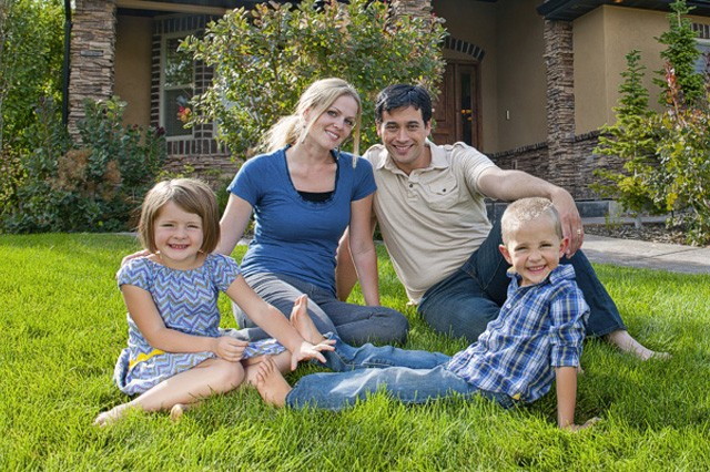 family sitting outside of home after receiving fha home loan